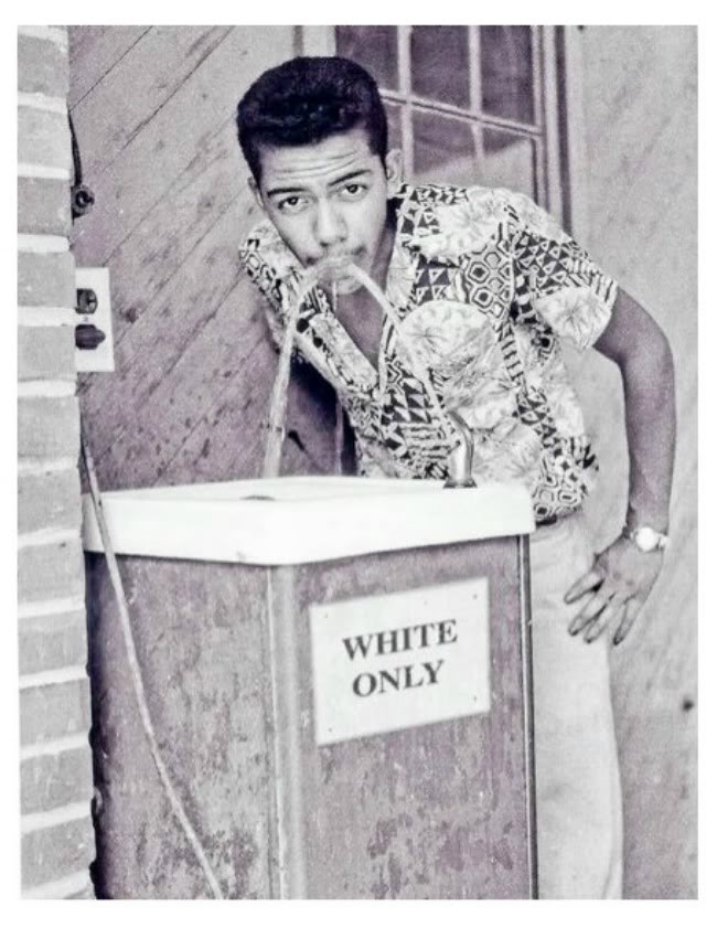 Black man drinking at white only fountain, ca 1964 by Cecil Williams