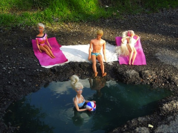barbie dolls using pothole as a beach