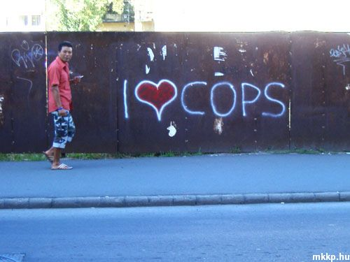 "Chinese boss in front of ""I love cops sign"" (earthlymission.com)"