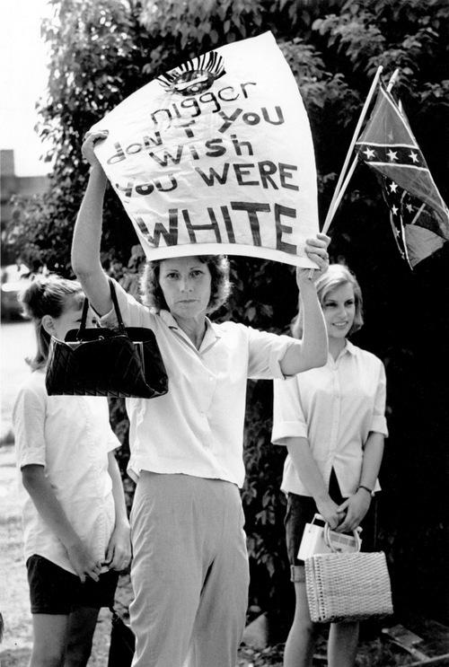 1965. A feketek egyik civil jogi felvonulasa menten lanyaival megjelent ellentunteto asszony. A tabla felirata Nigger ne akarj feher lenni. Bogalusa, Louisiana