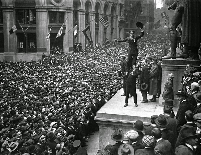 1918. Douglas Fairbanks Jr. holding up Charlie Chaplin in front of a huge crowd to promote Liberty Bonds. Wall Street, New York. [1918]