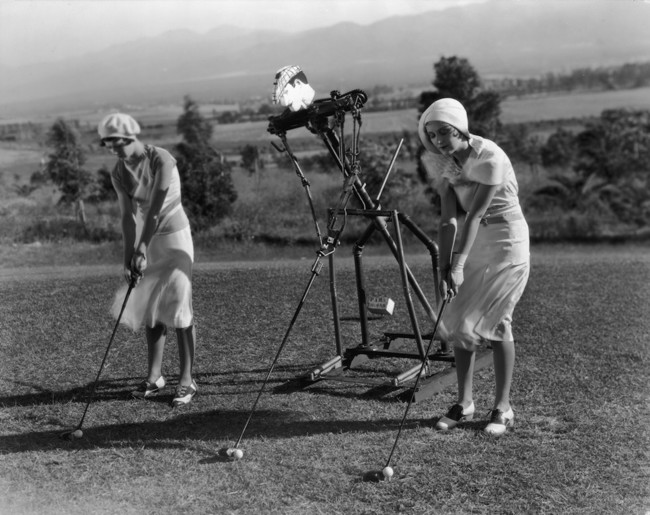 1925. Two ladies improve their aim by taking golf lessons from a 'robot' trainer. [1925]