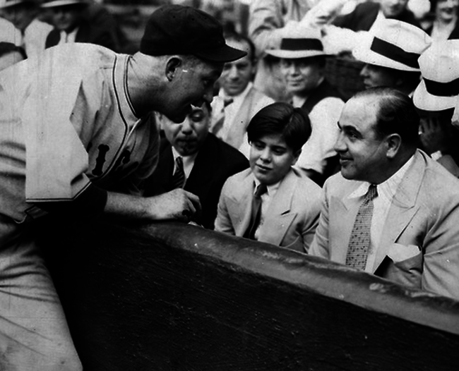 1931. Cubs catcher Gabby Hartnett signing a baseball for Sonny Capone, the son of Al Capone. [1931]