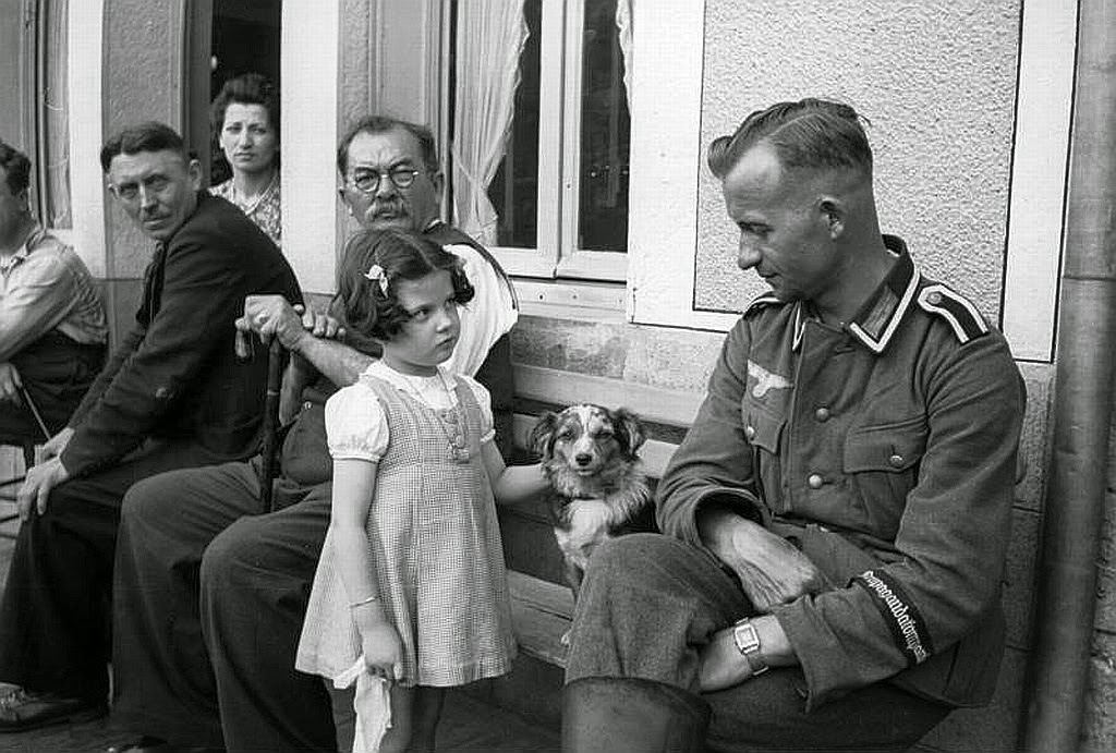 1941. A German soldier is eyed suspiciously by a young french girl (1941)