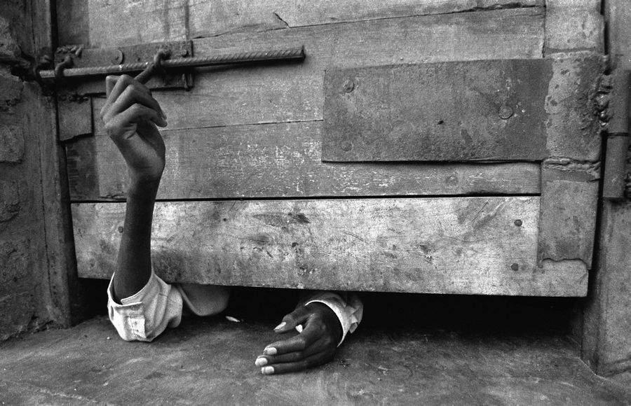 Man trying to open the door of his cell in Kigali during the genocide in Rwanda, 1994