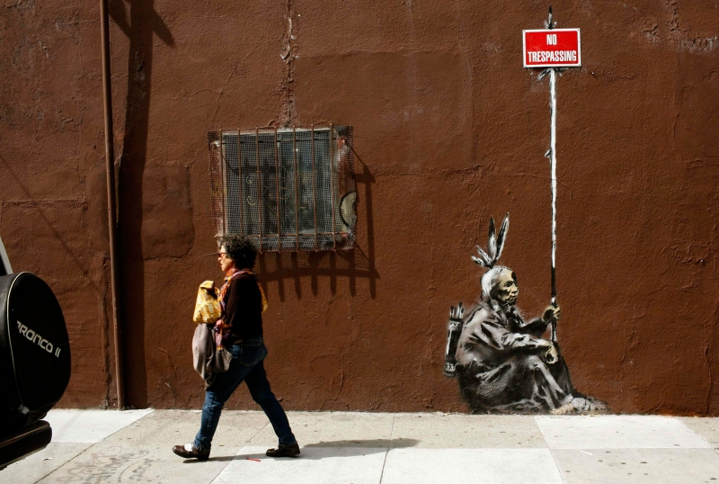 A woman walks past a drawing, believed to be the work of elusive British street artist Banksy, in the Mission District of San Francisco