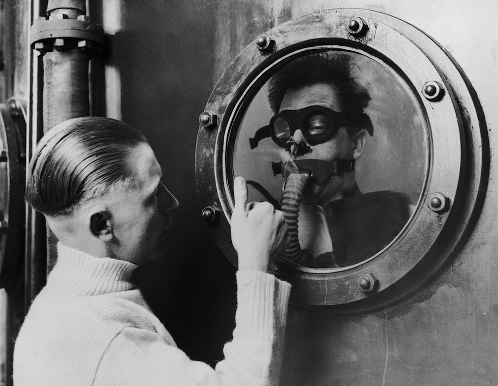 1939 An instructor signals through a porthole to a seaman at the bottom of a 15 foot tank, during submarine crew training at the DSEA Instructional Centre at Portsmouth in 1939