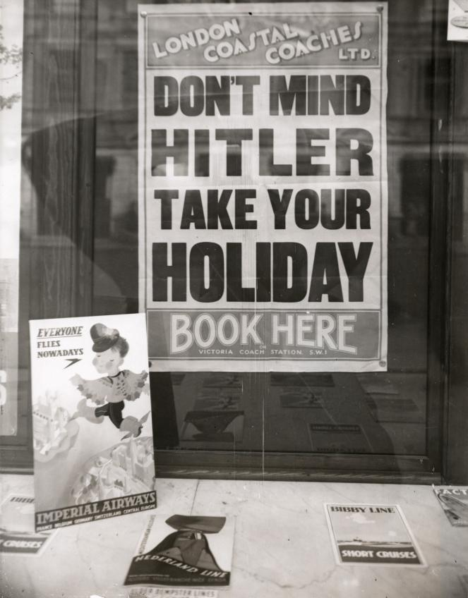 Poster in a London travel agency advising people to book their holidays in spite of the tense situation in Europe, 1939