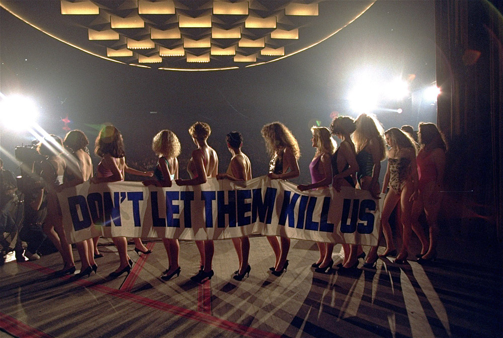 Participants in the Miss Besieged Sarajevo 93 beauty pageant line up on stage in front of a packed audience in Sarajevo Saturday The 13 contenders held a banner reading Don't Let Them Kill Us May 29, 1993