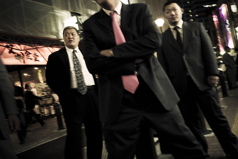 Members pose in the streets of Kabukicho, the red light district in the heart of Shinjuku, Tokyo, Japan. By always wearing tailored suits, the Yakuza attempt to spread an image of decency and conformity. But the underlying tension unmistakibly remains. Obvious influences are American gangster icons from the early 20th century, like John Dillinger.