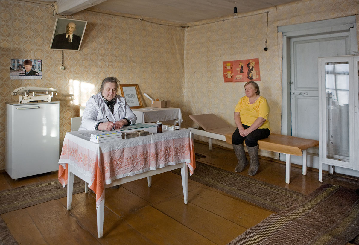 Dorfaerztin Elena Jegorowa mit Patientin Svetlana im Behandlungsraum, Leninplakat an der Decke