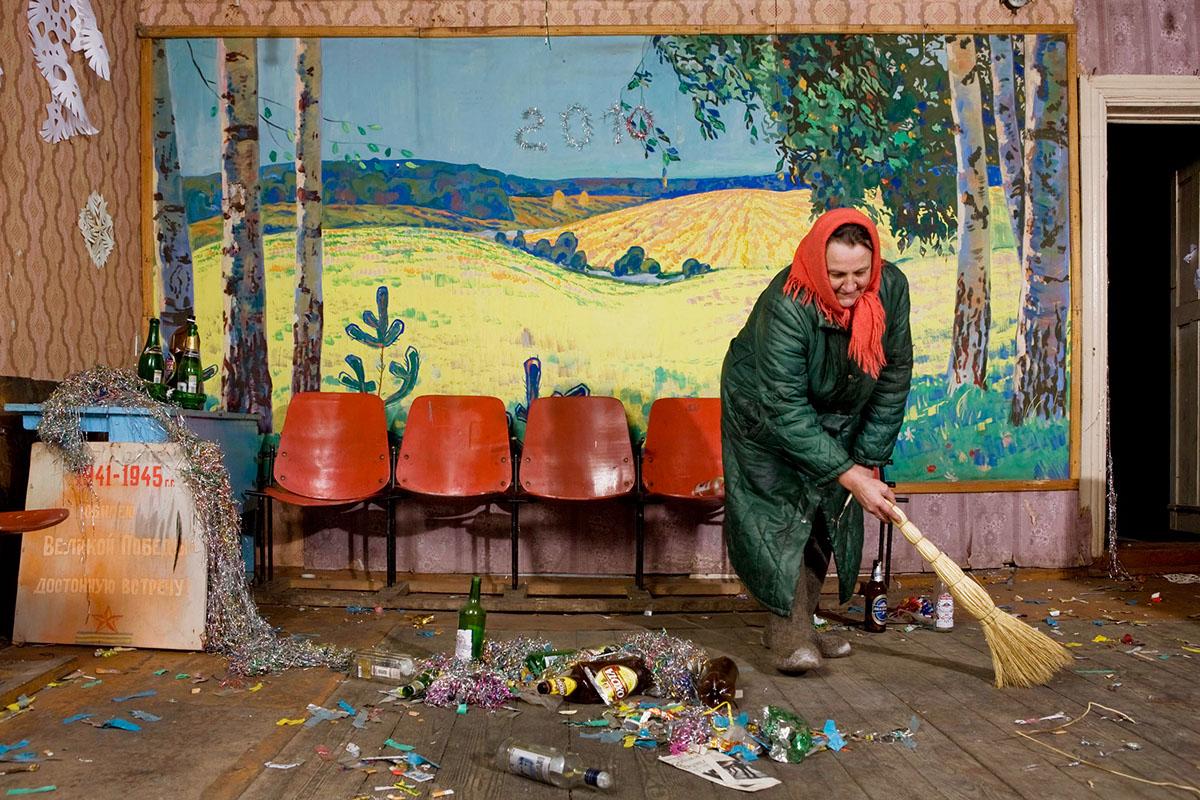 Elena Sergeja ,Saubermachen nach der Neujahrsfeier im Dorfklub, Wandgemaelde aus Sowjetzeiten von Künstler aus Bologe, naechste Stadt 30km, ganz links Tafel zur Erinnerung an den Sieg des zweiten Weltkrieges