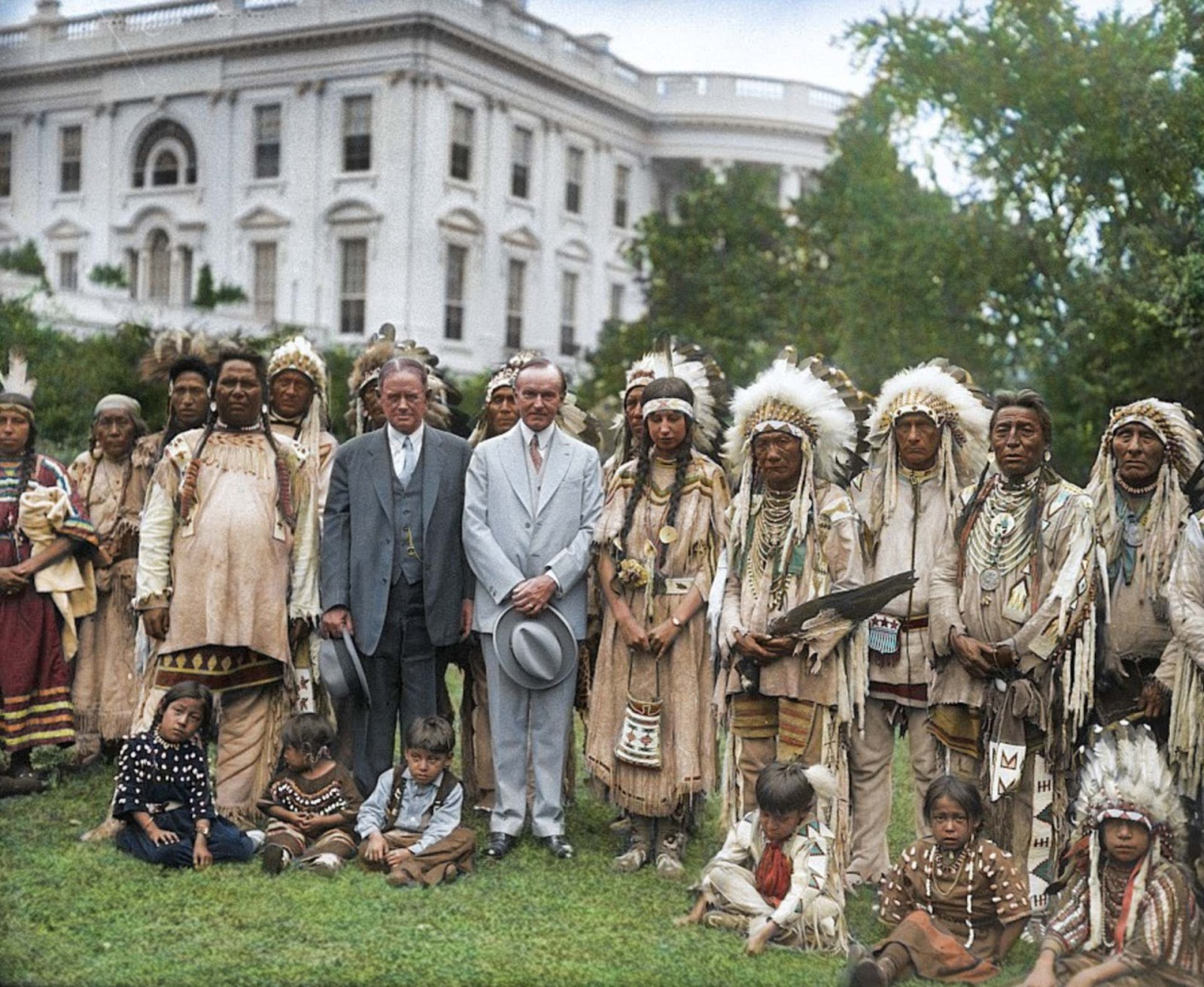 President Calvin Coolidge poses for a picture with a group of Native Americans outside the White House