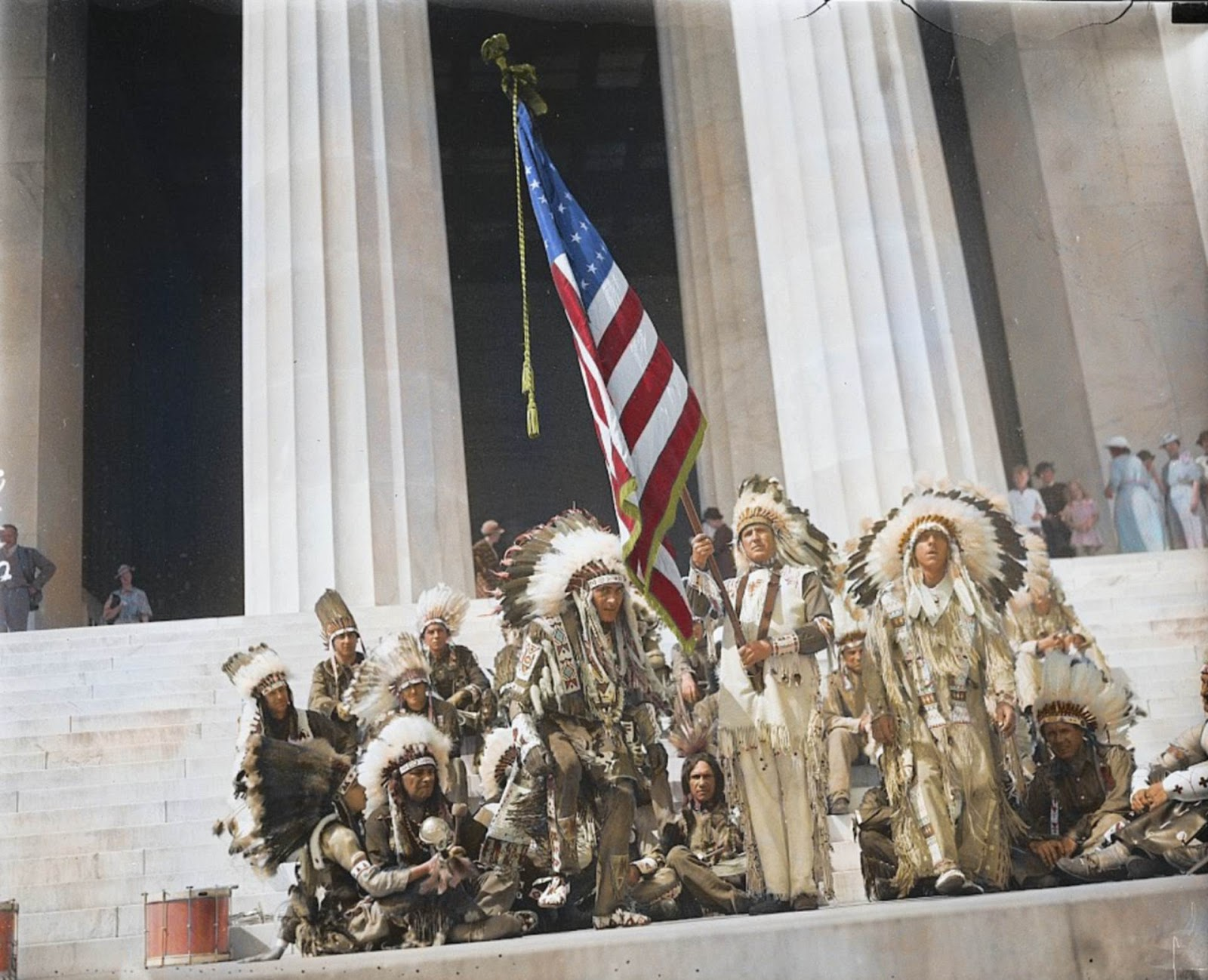 A group of Native American men wearing their traditional attire while raising the Stars and Stripes at the Lincoln Memorial in 1936